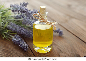 Essential lavender oil with fresh flowers on wooden...