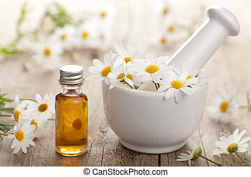 essential oil and camomile flowers in mortar
