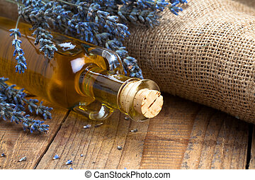 Essential oil bottle and lavender flowers, on wooden...