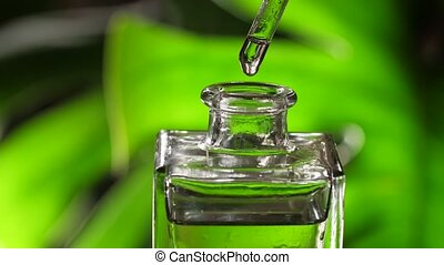 Essential oil or water dropping from pipette to the bottle.
