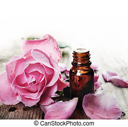 Essential Oil - Essential oil with rose petals on wooden ...