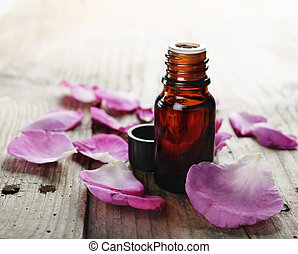 Essential Oil - Essential oil with rose petals on wooden...