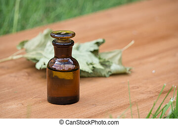 essential oil in little bottle and medical flowers herbs