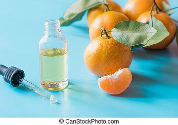 Essential oil of orange mandarin in glass bottle over pastel blue background. Skincare concept.