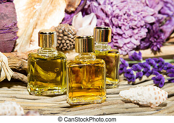 Essential oil or perfume, with lilac blossoms on a wooden...