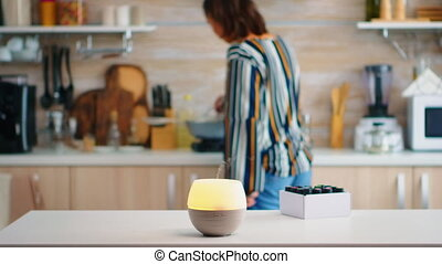Essential oils diffuser distributing aromatherapy while woman walks in the kitchen. Aroma health essence, welness aromatherapy home spa fragrance tranquil theraphy, therapeutic steam, mental health treatment