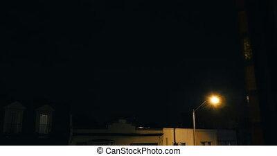 Establishing shot of a city environment during a lightning...