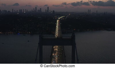 Establishing Shot of Bridge leading into the City of Istanbul at Dusk with Skyscraper Skyline Silhouette, Aerial Establisher forward