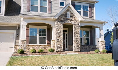 Establishing shot of generic luxury home in suburbia pan to...