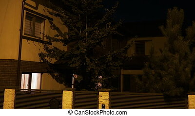 Establishing shot of residential house with lights turning...