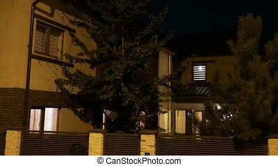 Establishing shot of residential house with pine trees in...