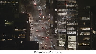 Establishing shot of sparse traffic in a modern city late at night.