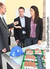 Estate agent handing keys to couple