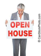 Estate agent holding and looking at sign for open house