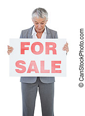 Estate agent holding and looking at sign for sale