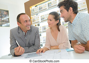 Estate agent in consultation with young couple