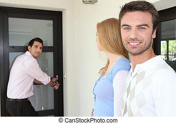 Estate-agent opening door to show home