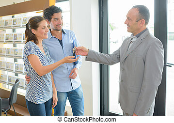 Estate agent passing keys to young couple
