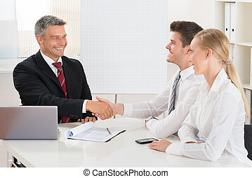 Estate Agent Shaking Hands With Couple