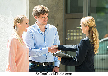 Estate Agent Shaking Hands With Young Couple