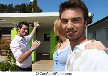 Estate agent showing a couple a house