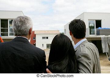 Estate agent showing a couple a housing development