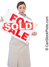 Estate agent showing for sale sign with sold sticker across ...