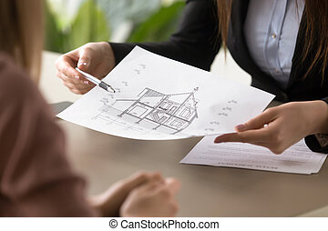 Estate agent showing house plan to client, signing rental agreem