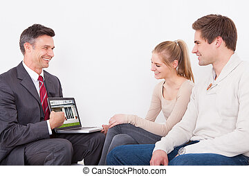 Estate Agent Showing Laptop To Couple