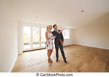 Estate Agent Showing Young Woman Around New Empty Property