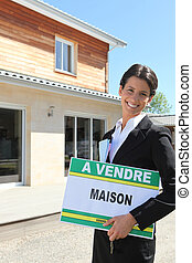 Estate agent standing in front of a house