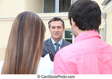 Estate-agent welcoming couple