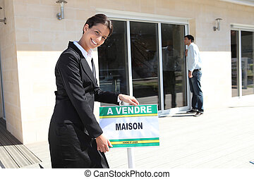 Estate agent with a French for sale sign