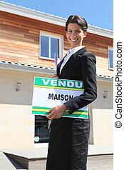 Estate agent with a vendu sign