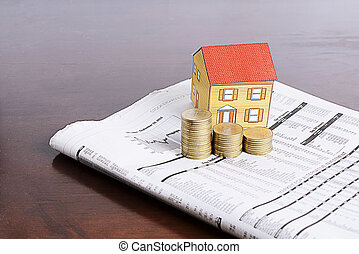 Estate investment concept with paper house and coins stack  on news paper on wooden table