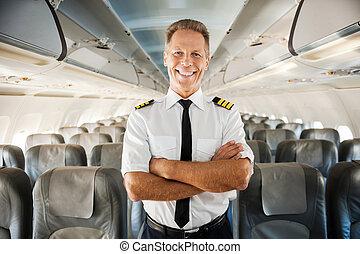 este, é, meu, plane., confiante, macho, piloto, em, uniforme, mantendo, braços cruzaram, e, sorrindo, enquanto, ficar, interior, a, avião