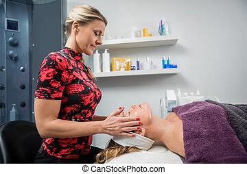 esteticista, dar, massagem facial, para, mulher, em, salão beleza