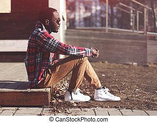 estilo de vida, moda, retrato, de, elegante, joven, hombre africano, escucha, a, música, tarde, y, goza, ocaso, llevando, un, hipster, tartán, camisa roja, y, gafas de sol, sentado, en perfil, aire libre