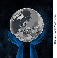 Estonia on globe in hands in space