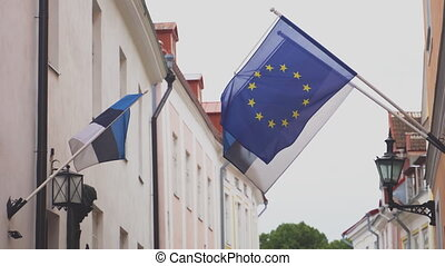 Estonian and EU flag on a flagpole waving on a house.