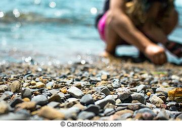 estreito, lavando, macro, sobre, foco, praia, fundo, ondas, tiro, cascalho, criança, tocando