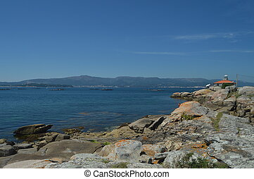 Estuary With Mussel Hatcheries In Its Interior In Front Of The Horse Point Lighthouse On Arosa Island. Nature, Architecture, History, Travel. August 18, 2014. Isla De Arosa, Pontevedra, Galicia, Spain.