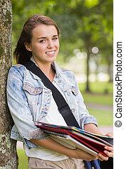 estudante, dela, árvore, jovem, alegre, livros, segurando, inclinar-se