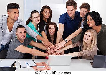 estudantes, empilhando, universidade, escrivaninha, mãos
