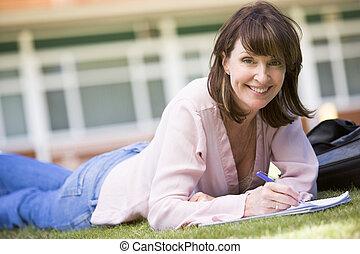 estudiante adulto, acostado, en, césped, de, escuela, con, cuaderno