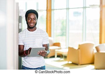 estudiante, con, tableta de digital, posición, en, biblioteca