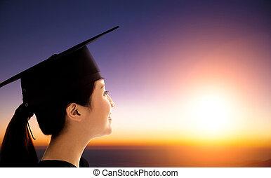 estudiante femenino, celebrar, graduación, mirar, el, salida del sol