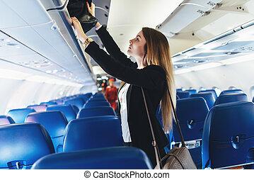 estudiante femenino, poniendo, ella, equipaje de mano, en,...