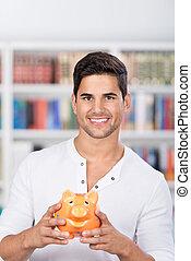 estudiante masculino, tenencia, piggybank, en, biblioteca