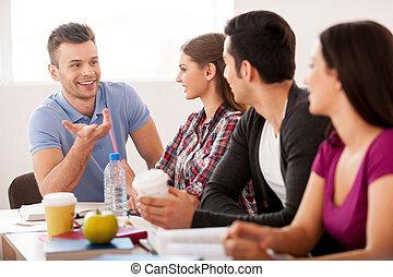 estudiantes, meeting., cuatro, alegre, estudiantes, hablar, uno al otro, mientras, sentado, en, el, escritorio
